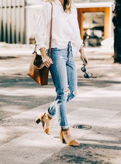 White shirt, distressed denim jeans with tan shoes and handbag.