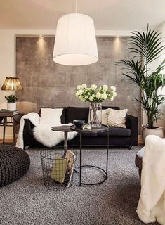 Pele sintética na decoração da sala de estar com sofá preto e parede de concreto aparente