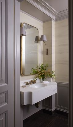 So many great details packed into this small powder bath: crown molding, wainscoting, wallpaper, curved marble sink! Tammy Connor Interior Design
