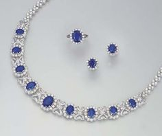 A SUITE OF SAPPHIRE AND DIAMOND JEWELLERY    Comprising a necklace, the front section set with nine graduated oval-cut sapphires each in a circular-cut diamond cluster surround, with diamond-set ribbon bow spacers, to the circular-cut diamond three-stone and brick-link backchain; a pair of earrings and ring en suite, mounted in platinum, necklace 44.5 cm