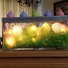 PartyLite candle holder decorated with grass and egg lights.