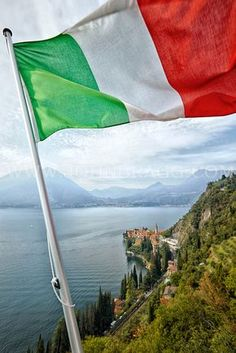 View of the Italian flag and mountains above Lake Como in Lombardy, Italy.