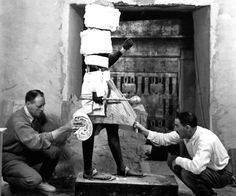 Howard Carter (on the right) working with his friend and colleague, Arthur Callender, on wrapping one of the two sentinel statues of the King found in the Antechamber before its removal to the 'laboratory' set up in the tomb of Sethos II. The statue shows the King wearing a headdress, kilt and sandals and carrying a mace and staff (November 30 1923)