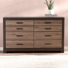 Looking for extra storage and a trendy addition to your master suite? This six-drawer dresser offers ample opportunity for stowing clothes as well as other essentials, and provides contemporary style with its two-toned wood design. While using it to tuck away linens and extra throw blankets in the guest bedroom, top it with a blown glass table lamp, a decorative ceramic vase, and a few fresh succulents for a cozy and glowing vignette. To bring a cohesive touch to the arrangement in your…