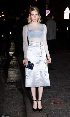 Elegant attire: Emma looked impeccable in a grey fitted top and silver A-line skirt as she...
