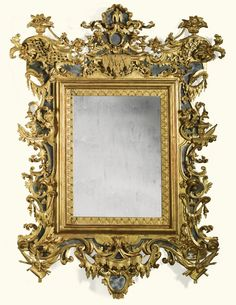 An Italian carved giltwood mirror, Venetian, circa 1730 with a shaped cresting with stylised fountain, scrolls, trelliswork, fruit-filled baskets and lambrequins, with a later rectangular plate within a lambrequin border with mirrored sides and apron, the whole carved with lambrequins, military trophies, drapery, vases and acanthus