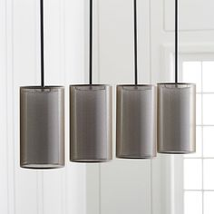 Contemporary chandelier layers on sophistication with double fabric shades and a lean, linear orientation. Eclipse suspends four cylindrical shades, each with a sheer outer shade veiling an inner white shade in transparent bronze. Slim rectangular ceiling plate and extension rods add to the clean look with a deep patina bronze finish.