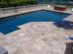 Dark blue pool with the Noce travertine tiles in a french pattern.
