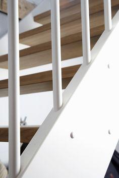 Öppen rak trappa med vitmålade vangstycken och spjälor.