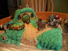 Lord of the Rings Cake. Simple using lego figures, frosting, cake, graham cracker crumbs and tootsie rolls for the door. Super simple.