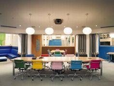 Escritório com cadeiras coloridas.