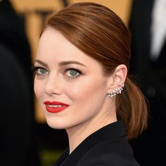 Emma Stone Start with damp hair and blow-dry straight. Create a deep side part and pull into a low pony. Secure with an elastic, and settle flyways with a thick pomade.