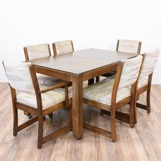 """This retro dining set features 6 chairs. The table is set on casters for easy moving. The chairs are upholstered in a cream and beige textured fabric. There is some wear on the wood. Just the right size for entertaining!    Dimensions:  Table: 56""""L x 36""""D x 29.5""""H   Chair : 20.5""""L x 19.5""""D x 35""""H (19""""H to seat) #retro #tables #diningset #sandiegovintage #vintagefurniture"""
