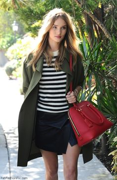 Rosie Huntington-Whiteley street style with military coat, leather skirt, striped blouse and Kurt Geiger handbag (October 2014).