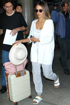 Jessica Alba wearing Louis Vuitton Soft Lockit Bag, Sunday Somewhere Soelae Sunglasses, Bric's Milano Spinner Trunk Suitcase, Birkenstock Arizona White Birko Flor Sandals and Molami Stitch Earbuds