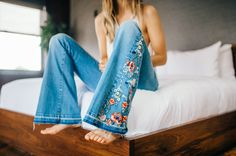 Farrah Embroidered Flare Inspired by decades past these denim flares feature beautiful embroidery detailing along the waistband and sides with an undone hem. This mid-rise style has a zip fly with button closure and is in a five-pocket style.