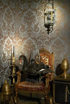Cole & Son Mariinsky Carmen 108-2010 - An ornate and graceful scroll work damask, screen printed using a subtle flecked metallic ink on soft chalky grounds of old olive, charcoal, grey, cream and mole, Carmen, takes its name from the well-known French opera by Georges Bizet. The design dates from 19th century France and based on its repeat, almost certainly originated from a silk weaving mill, probably around Lyon. It is produced here on a 68.5cm roll.
