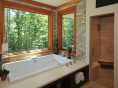 Stone walls around the tub and big, bright windows
