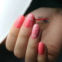 Delicate pink nail design with a pattern of flowers.