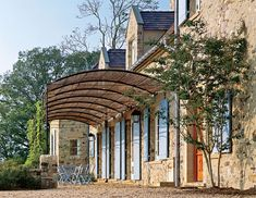 A pea-stone courtyard is shaded by a black iron tonnelle, or arbor, with a bamboo roof  - Traditional Home®