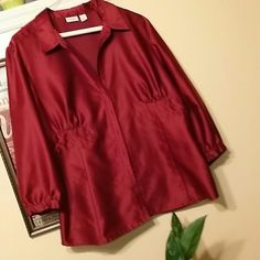 Cato size XL burgundy button up blouse 3/4 length sleeves that button at cuffs.  100% polyester.  Has a satiny like finish to it. Buttons stop into a deep v.  This blouse runs large.  I would definitely say it would fit great on a 1X up to an 18 depending on body type.  The burgundy is beautiful.  The detail shown in pic 2 goes around the entire top. Top worn a couple of times and is in great condition. Cato Tops Blouses