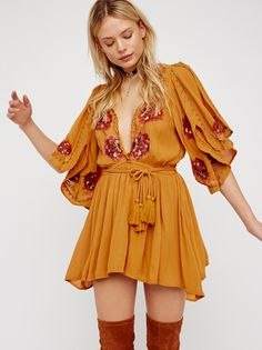 Cora Dress | Lightweight and crinkly mini dress featuring a plunging neckline with scalloped trim and beautiful embroidery detailing on the bodice and sleeves. The dramatic sleeves have a slit detailing and uneven edges. Elastic waistband for an easy fit with an adjustable wrap belt.