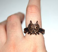 pwnlove:    Majora's Mask Ring  Wear the mask safely on your finger but just don't put it on your face or else, you'll go crazy and want to drop the moon on people. If while wearing, you get a sudden fascination with destruction and obsession with the ring, remove promptly or you could end up as Link's new nemesis or a Gollum knock-off. This ring available for pre-order by knil ($70).