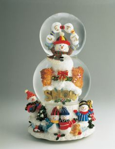 Close-up of a snowman and a Santa Claus in a snow globe