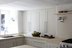 Long, white kitchen cupboards and corner worktop