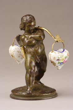 A very original French inkwell with a water carrier Cupid in patinated bronze. He is carrying two Paris porcelain pots, heart shaped, one for ink and the other for powder...
