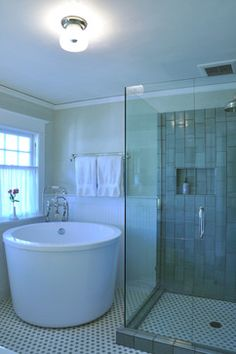 Round soaking tub with glass enclosed shower. May need to enclose it with a step or build a separate step