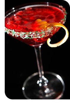 Mistletoe Martini (•1 ½ oz. citrus vodka  •¾ oz. pomegranate juice  •¾ oz. defrosted lemonade concentrate (strained of pulp)  •2-3 drops orange blossom water  •Ice  •Cava (or any dry sparkling wine)  •Shaker and strainer  •Martini glass  •Garnish: Equal parts red, white and green decorative sugar  •Pomegranate seeds  •Orange twist)