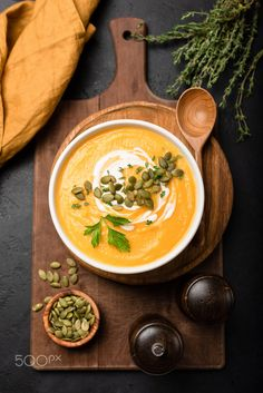 Pumpkin soup in bowl garnished with cream and pumpkin seeds. Top view. Autumn fall comfort food. Cream of pumpkin squash soup
