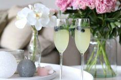 Een limoncello cocktail met home made limoncello, spa rood lemon, prosecco en een takje munt en blauwe bessen voor de decoratie.