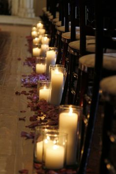 Mahogany chairs alongside white candles and contrasting flower petals | villasiena.cc