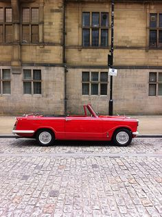 "Red Triumph Herald by Dilys Treacle Treasures on Flickr.  ""Spotted on Surrey Street, Sheffield. It was parked outside the Town Hall"". vintage car shiny red"