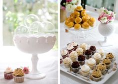 An engagement party dessert table with cupcakes, a croquembouche cake plate and a decorative ceramic bowl centerpiece filled with glass ornaments.