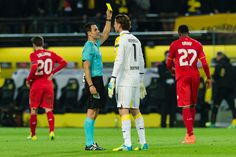 Goalkeeper Roman Weidenfeller of Borussia Dortmund is given a yellow card from referee Carlos Velasco Carballo