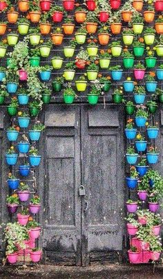 Different  Colored pots hanging on a wall around a door outside decorations