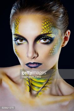 Attractive young woman in makeup snake shot in the studio