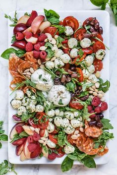 Burrata cheese, marinated mozzarella balls, tomatoes, and fresh stone fruit are laid out on a platter making this and easy self-serve salad or appetizer