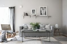 minimal layered scandinavian inspired living room in different shades of grey | black mid-century inspired wall sconce | Grey linen sofa | IKEA Karlstad sofa with a Bemz Loose Fit Urban cover in Graphite Brera Lino linen