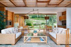 Os sofás com estrutura de palha (Vimoso) dão charme ao ambiente de estar, posicionado ao lado da sala de almoço, onde duas mesas de laca branca (serpa Marcenaria) foram cercadas por cadeiras de bambu do arquivo contemporâneo.