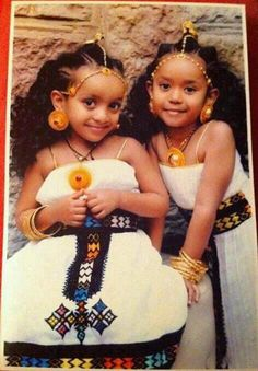 Ethiopian girls wearing traditional dresses & their mother's big traditional jewelery