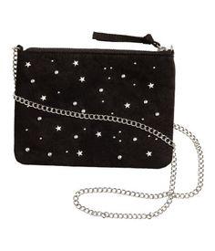 Zwart. Een schoudertasje van imitatiesuède met ronde en stervormige studs aan de voorkant. Het tasje heeft een ritssluiting en een schouderketting van