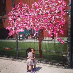 this is one of the most beautiful and happy guerilla wool art installations I have seen and what a lovely photo too, hug to all crochet cherry blossom flower yarnbombing art
