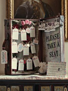 escort cards in suitcases with luggage tags and mini pegs