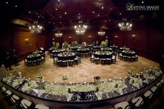 Green, black, & white ballroom with dance floor between long head table and circle guest tables - green & black damask table runners and green floral | Lasting Images Photography | villasiena.cc