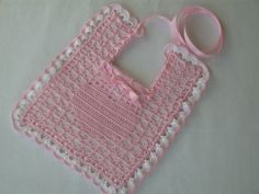 """It has a White side and a Pink side. It measures aprox. 9"""" x 7"""" and a Heart motif shows in the lacet on one side and the double crochet stitches on the other. The edges are double crochet scallops all around and accented in Pink. A Pink 1/8 inch ribbon is fed through the outside eyelets and 3/8 inch ribbon is fed through the eyelets around the neck.  Functional, Dainty, Sweet, comforting, and protects clothing!"""