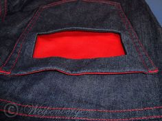 GARETH are straight cut jeans with a second pocket in the left hip pocket. You can see the red cotton fabric through the pocket mouth.